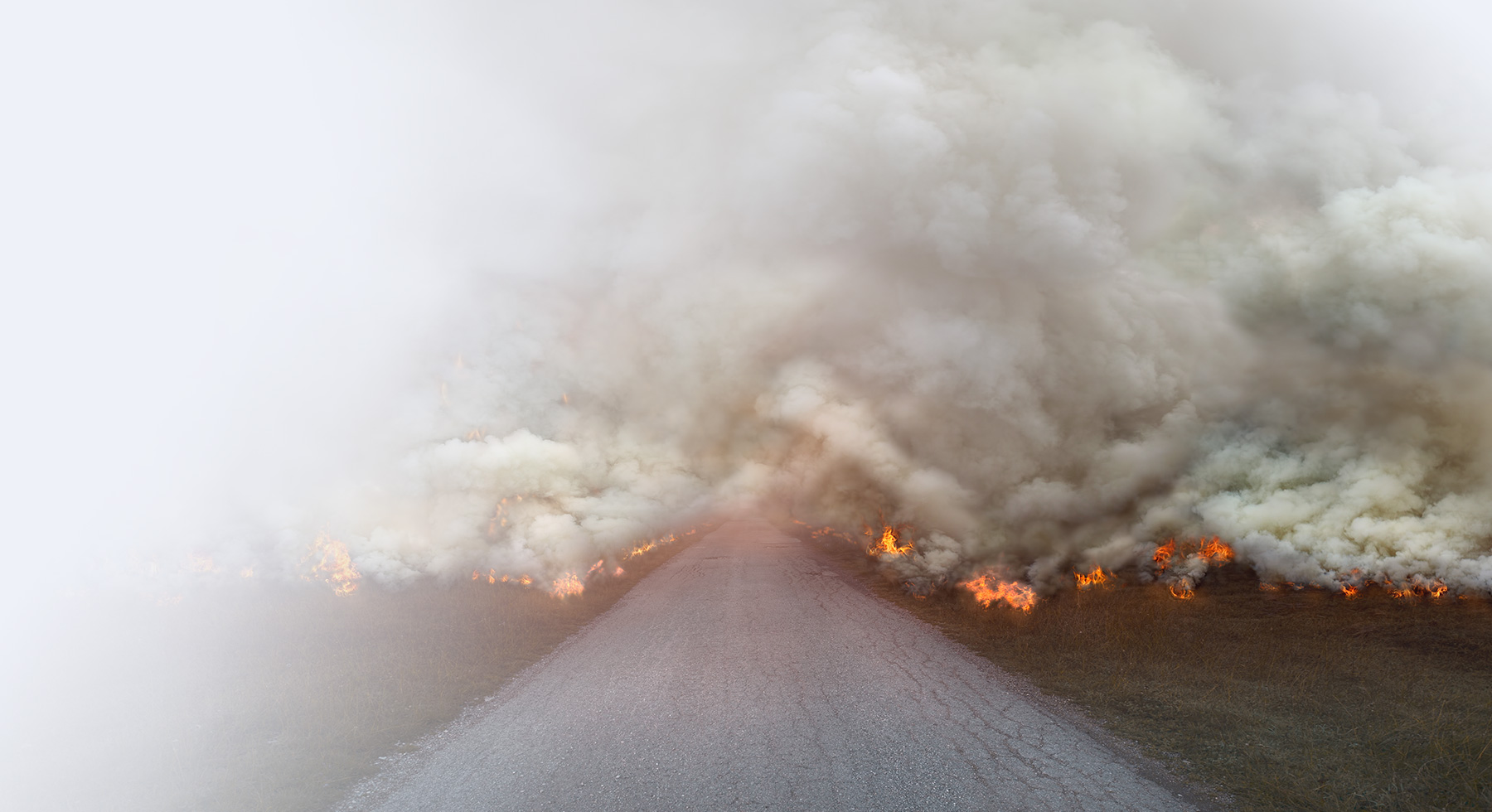 Fire burns with large smoke clouds on the road.