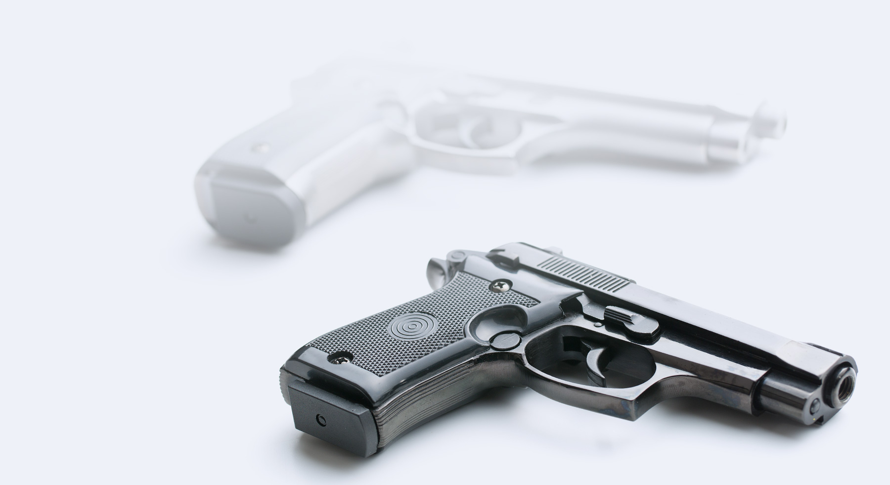 Hand gun on a blank white background with fading shadow in the background.