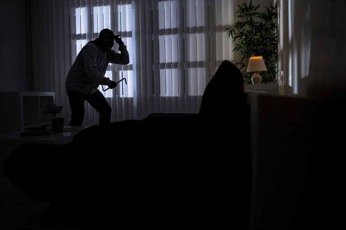 Home intruder creeps through the living room of a home.