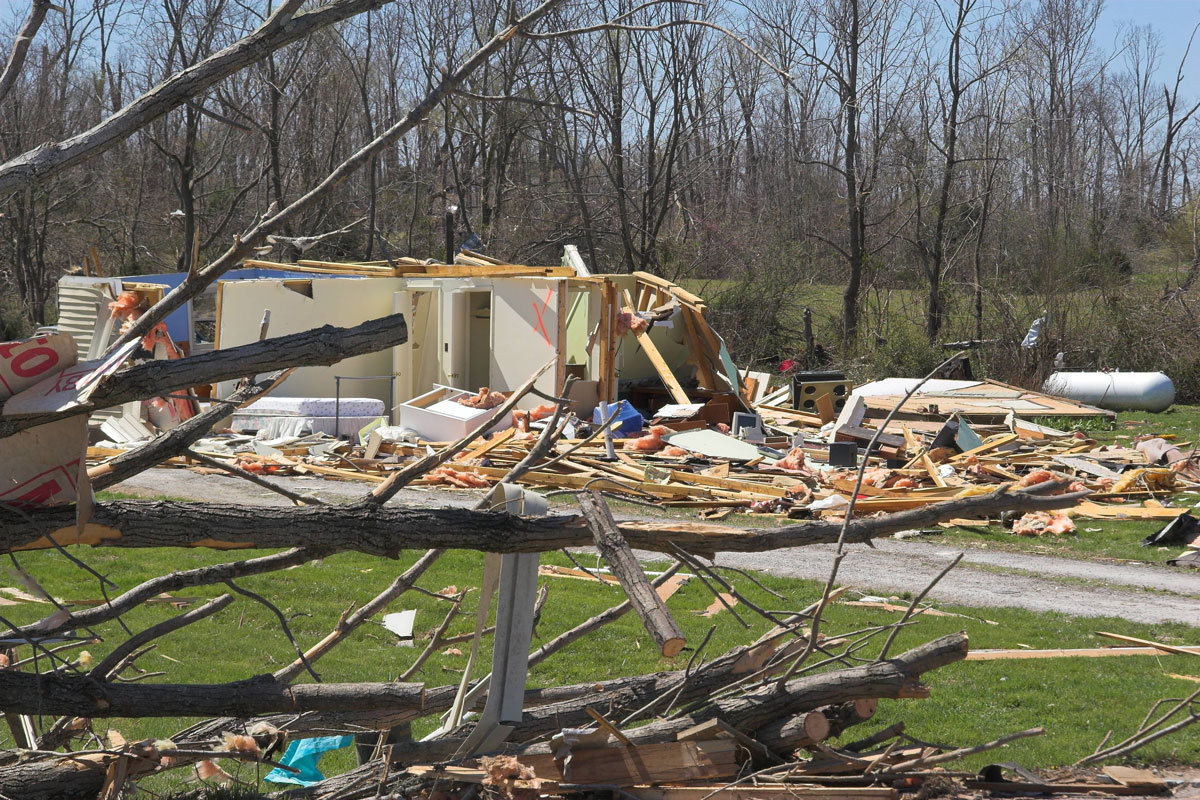 Tornado damage destroys a home, debris are strewn everywhere.