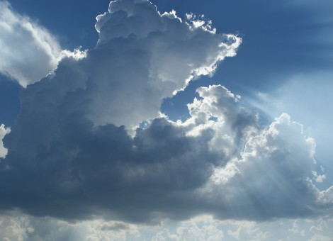 Light rays burning through large clouds in the sky.