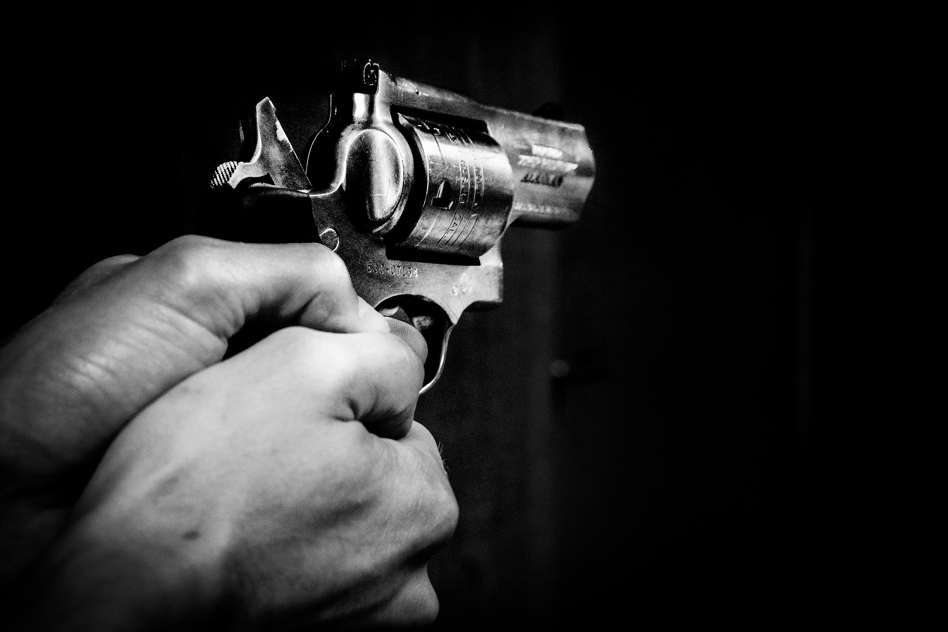 gun in the dark with light on the hands holding it