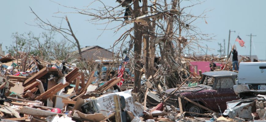 A tornado destroyed a town and a man raises a flag in the background.